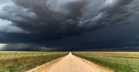 Donker wolken in een weiland boven een weg
